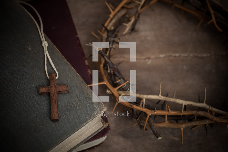 cross necklace on a stack of books and crown of thorns