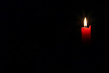 red candle in darkness