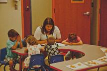 A teacher praying with children in Sunday School.