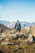 man hiking on a rugged mountain landscape carrying a Bible
