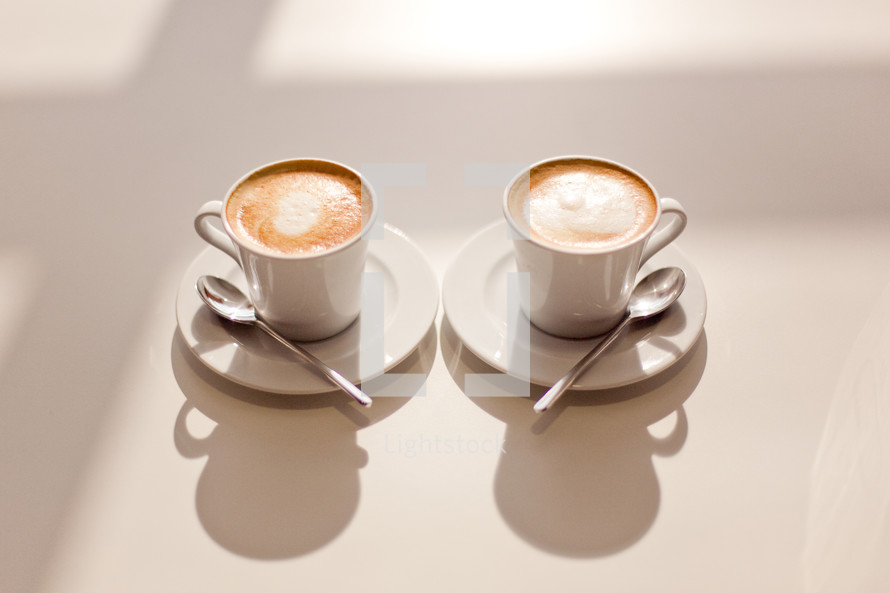 Two cups of coffee sitting in the sun on a white table
