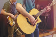 worship practice with acoustic guitar and bass on stage