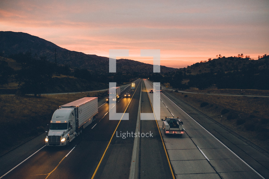 passing cars and semi-truck on a highway at dusk