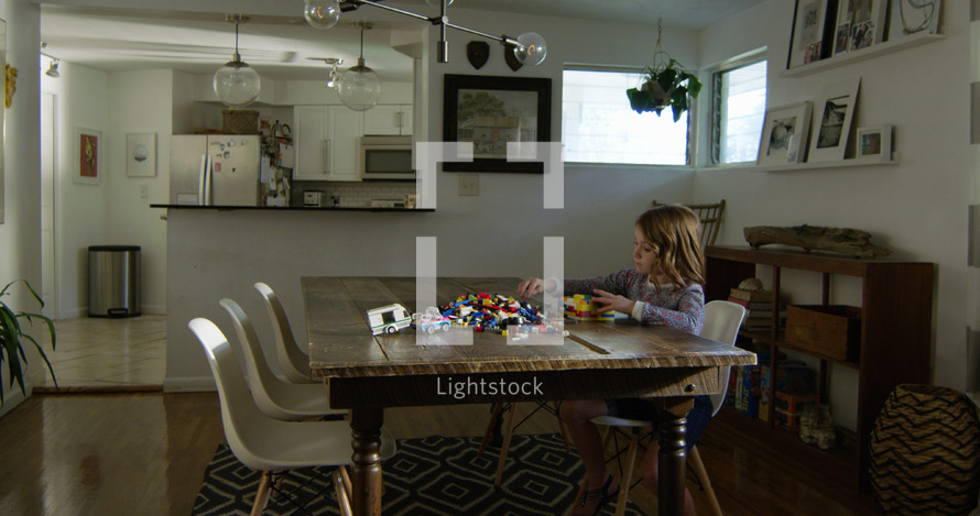 a child with building blocks at a dining room table