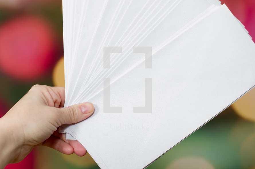 hand holding white envelopes