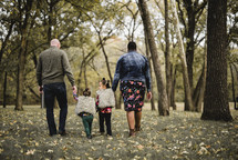 a family walking holdings hands in a park in fall