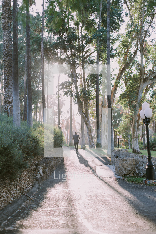a man jogging on a path in a park
