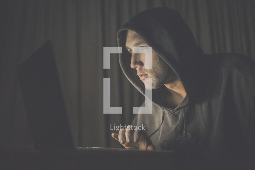 A man in a hooded sweatshirt using a laptop computer.
