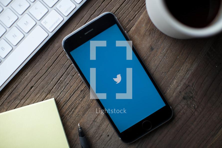 Twitter app on a cellphone screen on a desk