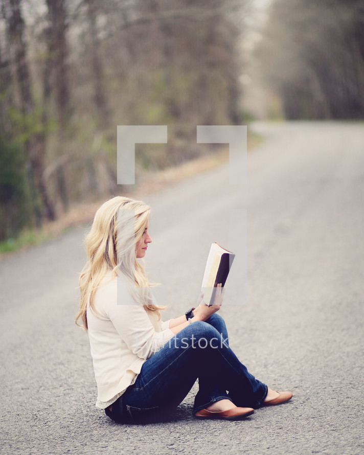 Woman sitting with legs crossed in the middle of the road reading the Bible.