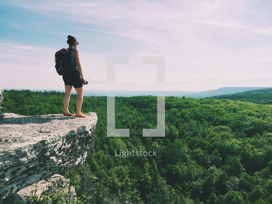 woman standing at the edge of a mountainside