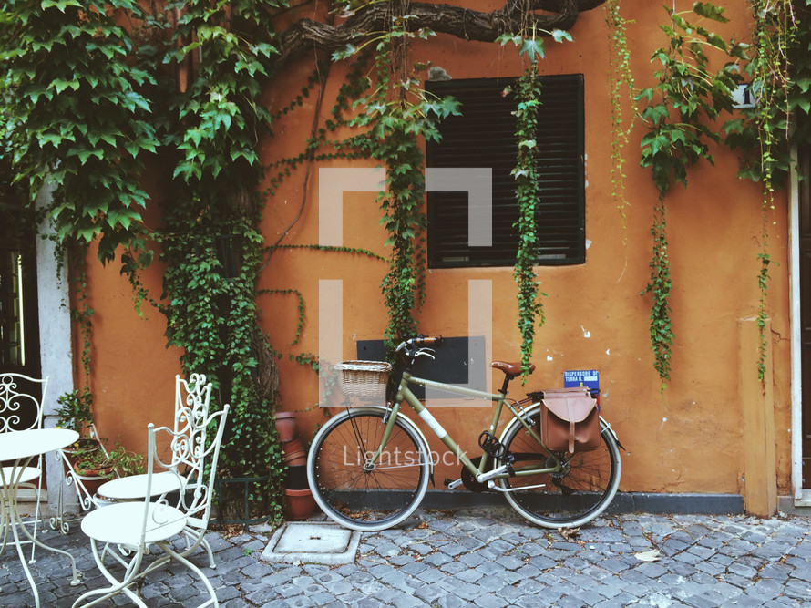 bike leaning against a wall and out seating on a patio