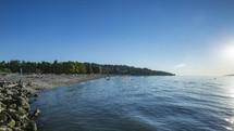 sunbathers on a lake shore