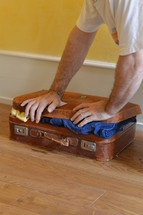 man trying to close his overstuffed suitcase
