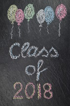 chalk on slate with balloons and the words: class of 2018