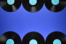 border of old black vinyl records with blank cyan labels on blue background