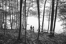a couple standing outdoors by a lakeshore