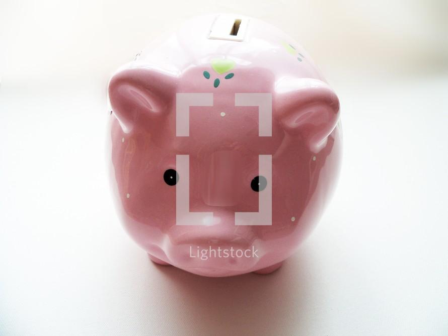 The front view of a piggy bank staring out against a white background encouraging people to save their money for the future for college, vacations, education, emergency funds or retirement.  Saving money is a discipline and when financial crisis occurs, we need to have savings to depend upon without having to borrow money from lenders and be able to meet our financial needs. Our heavenly father promises to provide for us in our time of need and even when we don't have need but we still need to be good stewards of our money and savings and invest properly to plan ahead for the future.