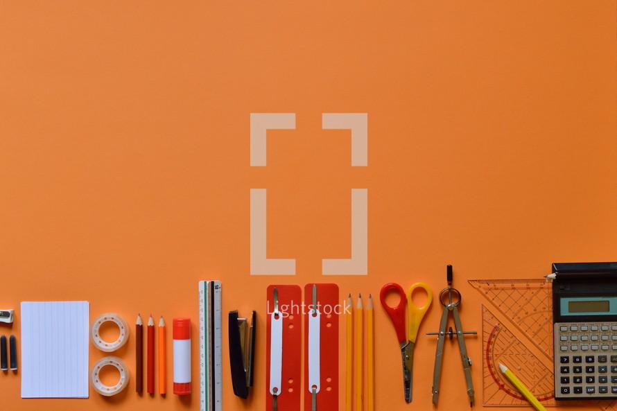 Office or school supply border on orange paperboard
