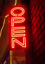 A Neon Open sign lights up the night in neon orange surrounded by Christmas lights illuminating a brick exterior building in a downtown retail area telling passer-bys that the store is open for business and welcoming the public during the shopping retain season..