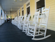 A line of white rocking chairs on a long wooden front porch in a rural country setting.