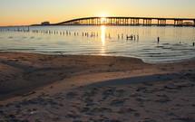 Sunset beyond a bridge by a beach.