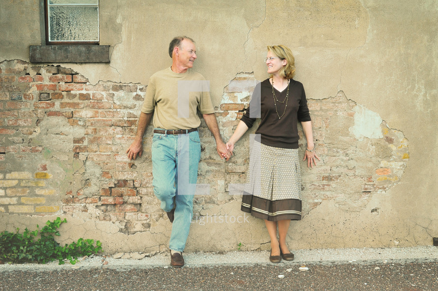 Couple holding hands while standing against an adobe house.