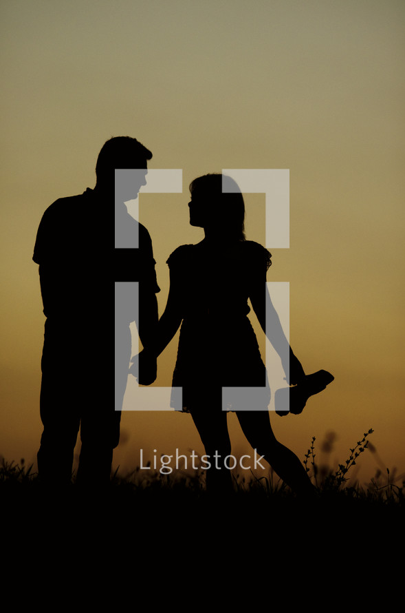 Silhouette of a couple holding hands while standing in a field at sunset.