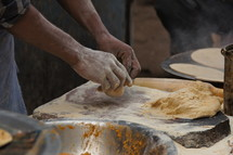 Man kneading dough in an indian bakery