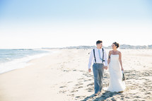 bride and groom standing on a beach