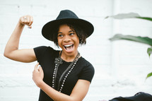 An African American woman in a black hat flexing her muscle