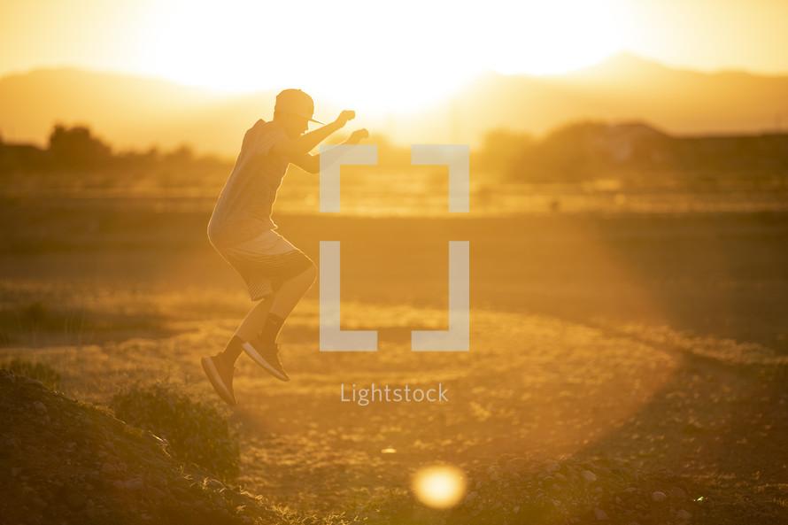 teen boy leaping in warm sunlight