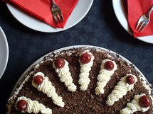 Black forest cake surrounded by plates and napkins ready to be eaten.