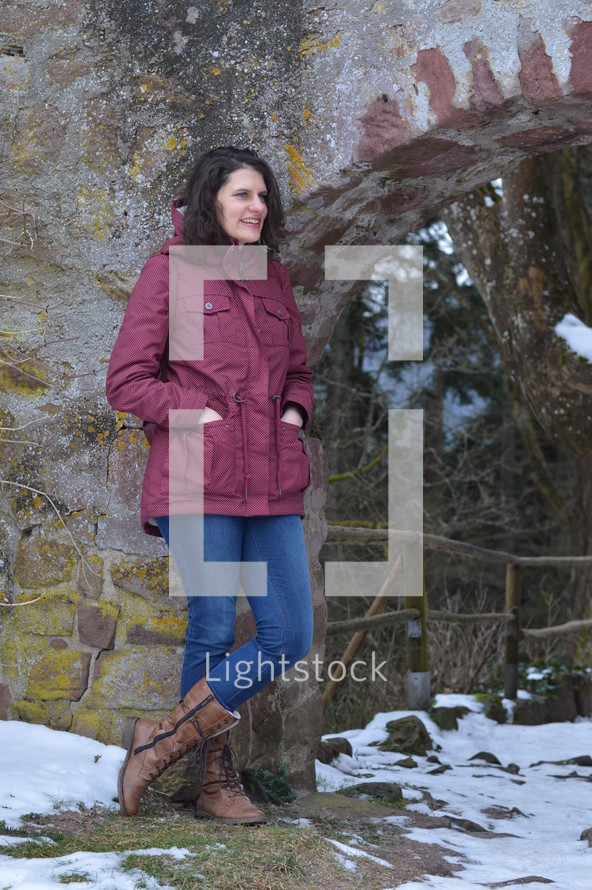 a woman standing outdoors in a coat in the snow