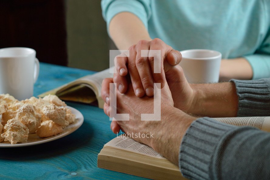 couple holding hands and praying over open Bibles