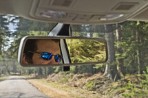 reflection of a man in sunglasses in a rearview mirror