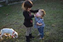 a little girl feeding her brother a sucker
