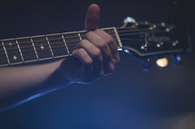 hands on a guitar neck