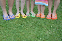 feet in colorful flip flops standing in the grass
