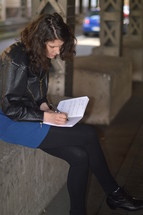 a woman sitting and writing in a journal