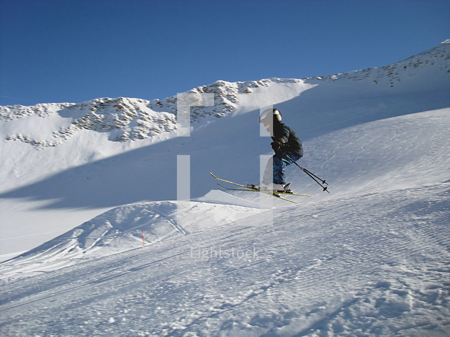 a little six years old boy jumping on his ski,