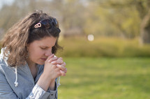 Young brunette woman praying outdoors.