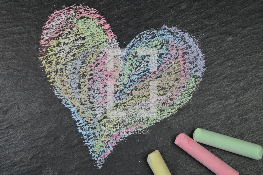 heart shape in sidewalk chalk on slate with chalk sticks