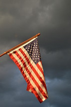american flag hoisted up on flagpole in front of dark rainy cloudy sky while a storm is brewing