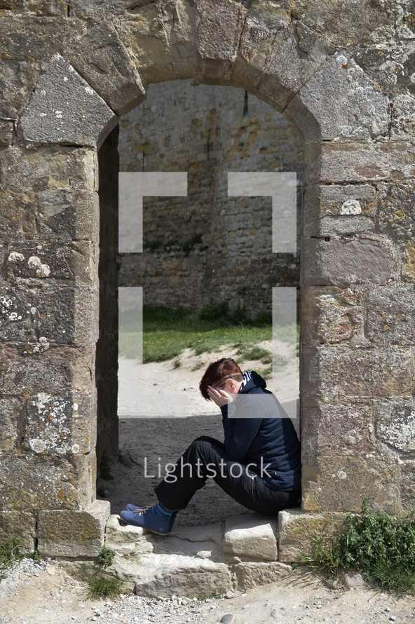 woman in grief sitting on the floor in an archway
