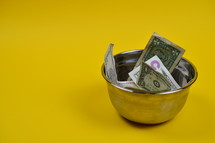 dollar bills in a bowl on a yellow background