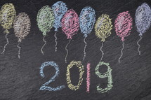 chalk balloons on slate with the number of the year 2019