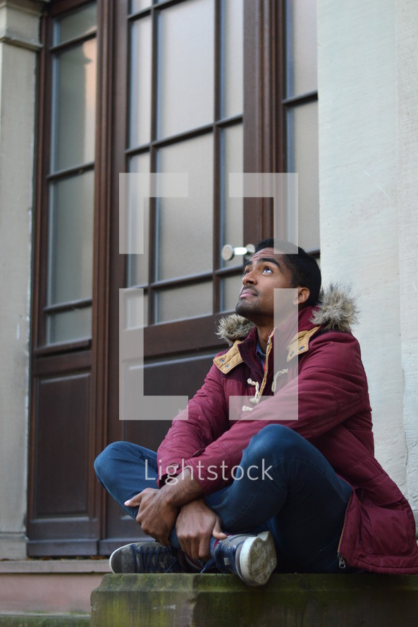 man sitting on steps in front of a church looking up