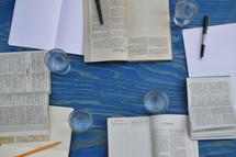 small group bible study with different bibles, notebooks, pens and glasses on a blue wooden table