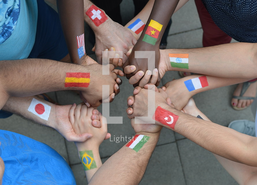 International brothers and sisters in Christ standing in a circle together and holding hands
